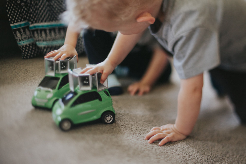 Twins playing with toy cars