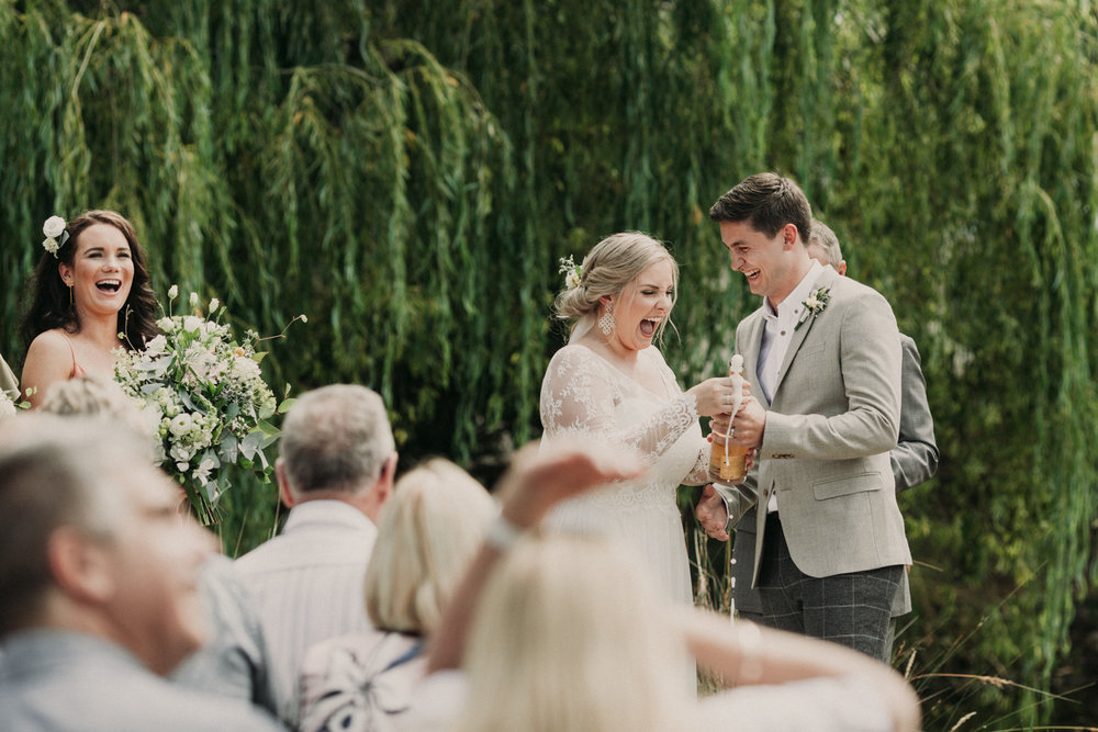 Bride and Groom pop a bottle of Champagneon their wedding day