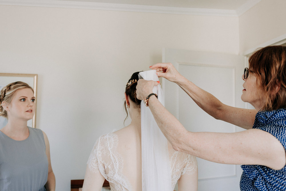 Bride putting on her wedding veil