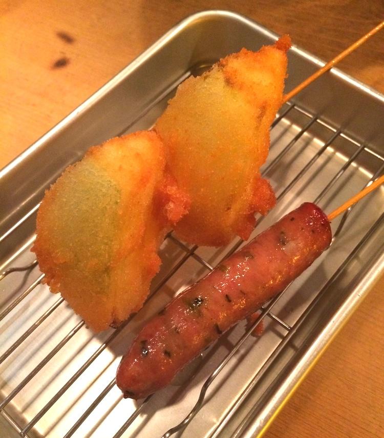 Panerad och friterad gul lök till vänster, wasabi-kryddad korv till höger, friterad utan panering.