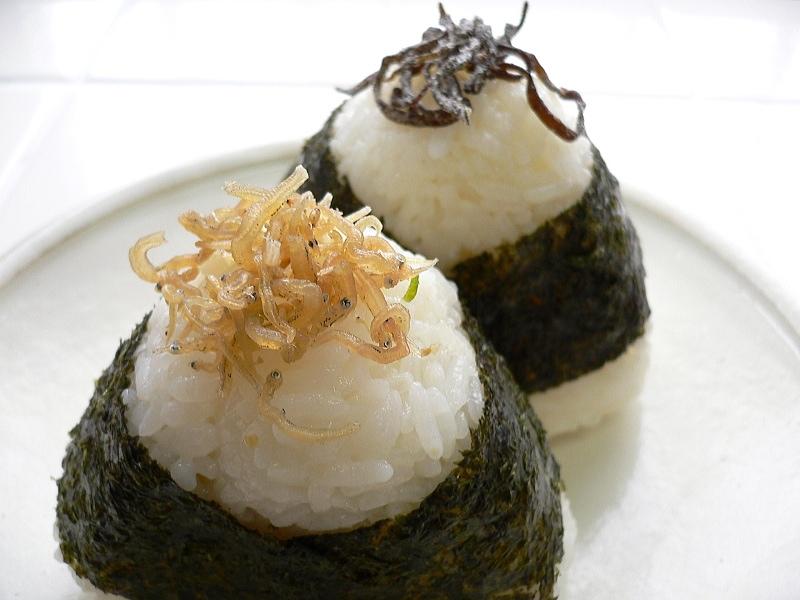 Här har vi ett par hemlagade risbullar (då man ofta lägger lite av inkråmet ovanpå bullen för att indikera vad det handlar om). Längst fram har vi kokta fiskyngel och där bakom brunalgen kelp.  Foto: Wikimedia Commons