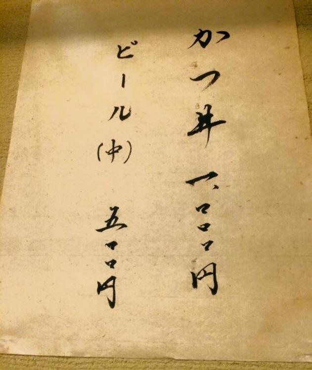 När japansk text är lodrät, läser man från höger till vänster. Här katsudon - friterat fläskkött på risbädd - till höger och en halvliter öl till vänster.  Foto: Akihito Mochizuki