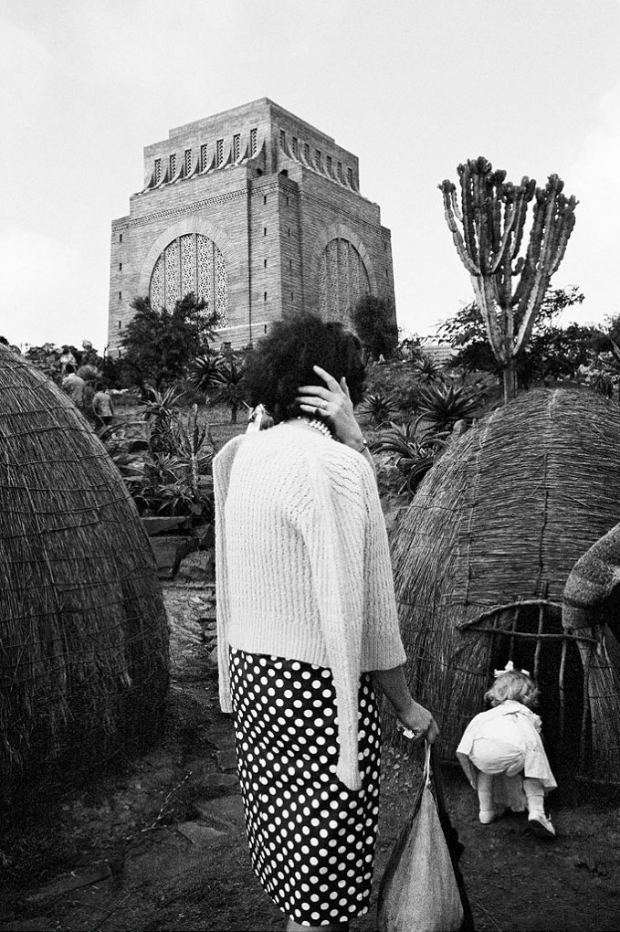 Child with a replica of a Zulu hut at the Voortrekker Monument, on the Day of the Covenant, Pretoria (3_9248) , Dec 1963, Gelatin silver print by David Goldblatt. Michael Stevenson Gallery