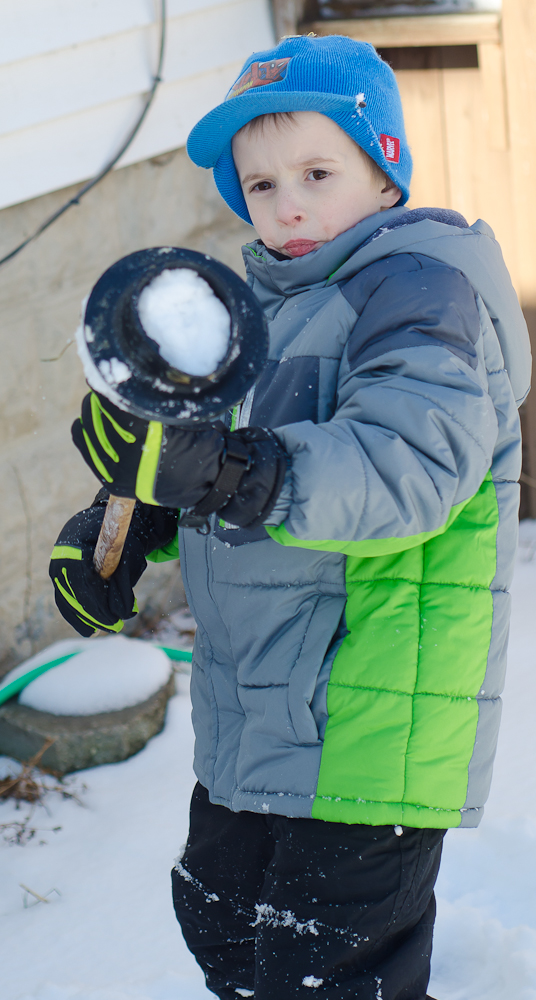 1.6.15    Nikon D7000 with Nikkor 50mm f/1.8 lens; f/3.5; 1/640; ISO 100  The boys played outside in the snow for almost two hours after lunch. It looks like Anderson found a new use for a plunger - snow bomb launcher!