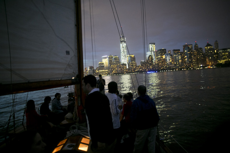 Guests enjoying an evening cocktail party sail next to the glow of Ventura's midships hatch.