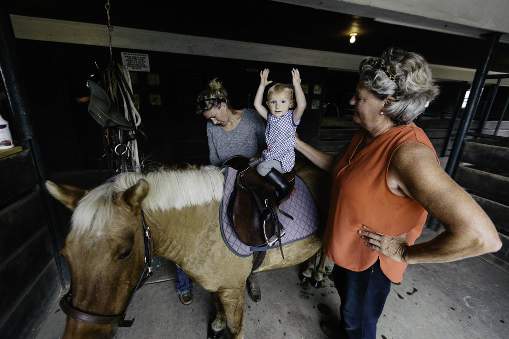 "Tootie, her daughter Rece Nester, and granddaughter Adelyn in the horse barn. ""Riding is part of the fabric of who we are. it's good therapy, it's really healthy and it's what keeps us happy. There's nothing quite like it."""