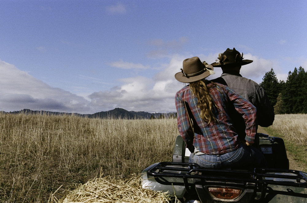 "Erik Markegard and ranchhand Suzanna ""Suey"" Hall ride over to feed the herd. - Jenner, CA"