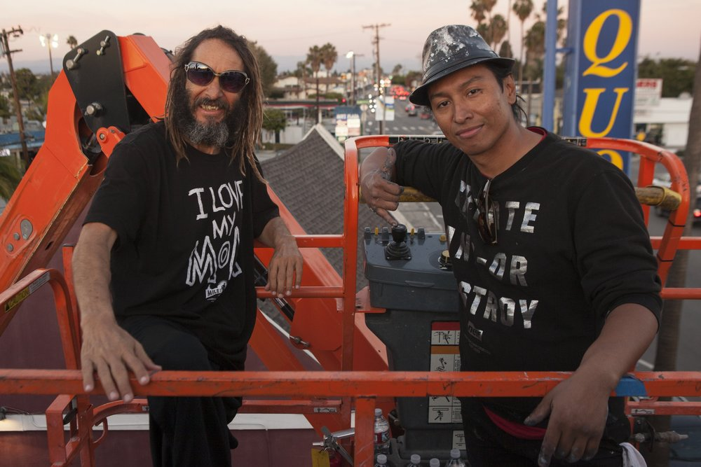 Robert Vargas and Tony Alva in a lift at The Kinney Venice Beach after Robert painted Tony live in his mural Warrior Legend
