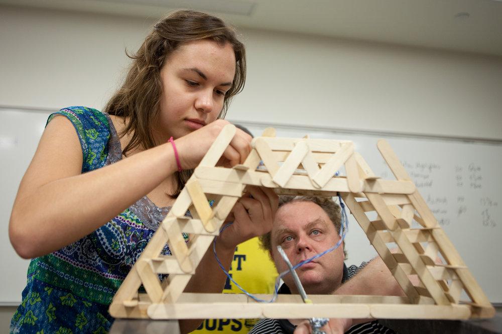 M-STEM participants test the load capacity of the bridges they built.