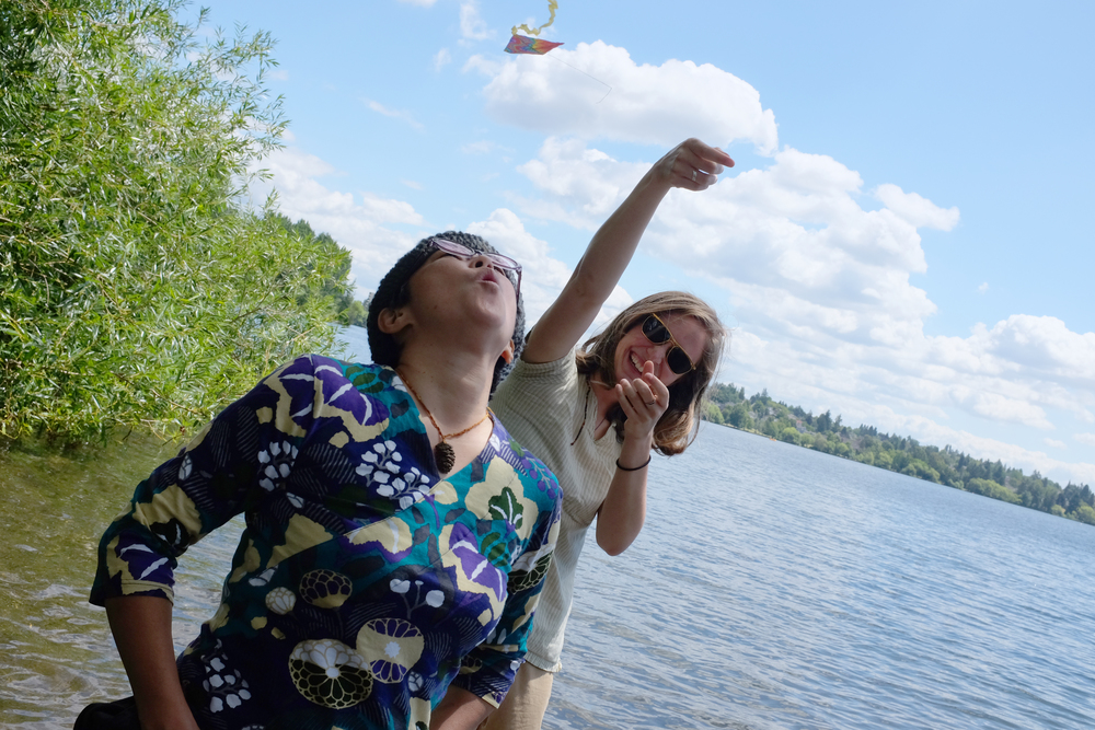 Our friend Alex holds a tiny kite while Reiko tries to make it fly by blowing on it. Green Lake Park, Seattle.  Photo by Shishido.