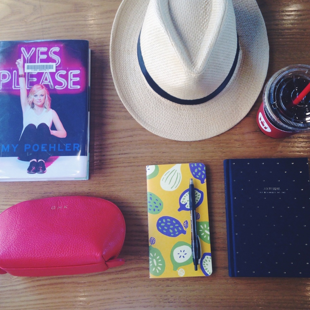 Essentials for a cafe trip: current read- Amy Poehler's Yes Please, makeup bag, journals, pen, panama hat, and an iced americano.