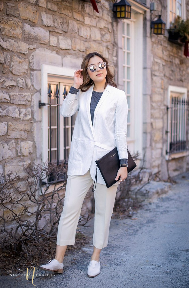 heydahye standing in front of old montreal brick wall posing in grey top and white blazer