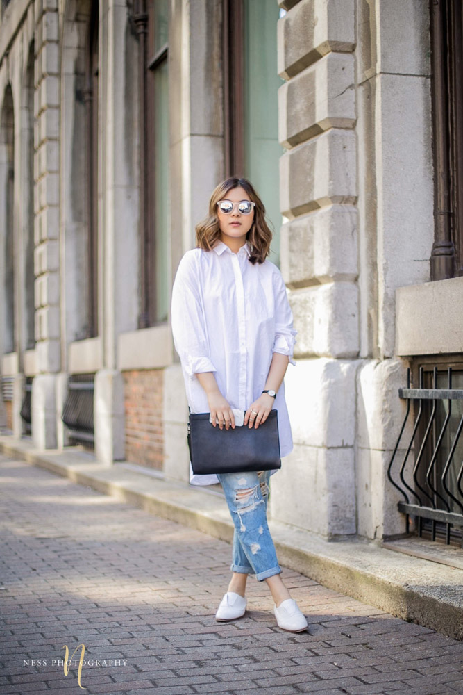 photo  of lifestyle blogger heydahye in the streets of montreal old port wearing ripped jeans and white shirtdress