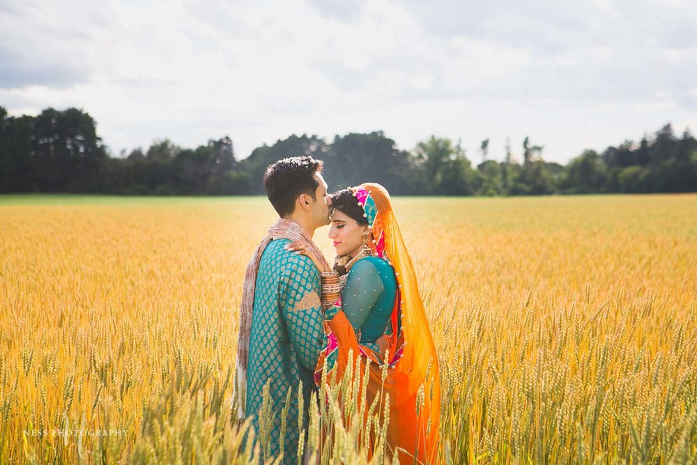 bride and groom hugging in wheat farm during pakistani wedding bridal shoot in ottawa