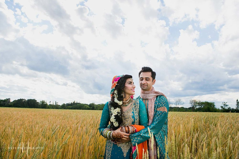pakistani bride and groom wearing bleu sherwani and lehenga in industrial farm in ottawa holding each other