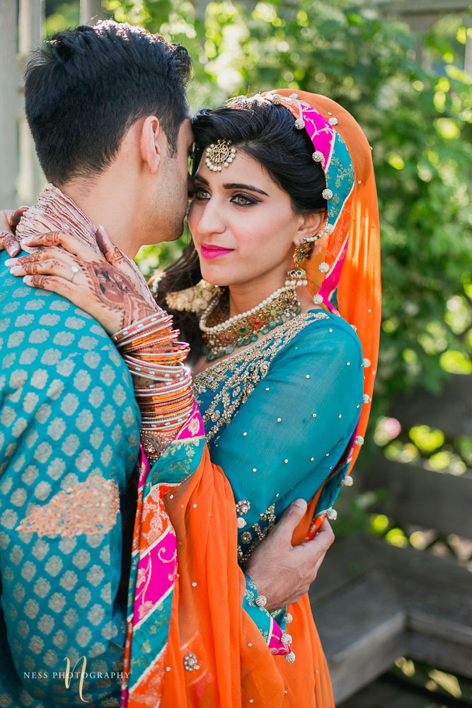 bride with orange dupatta putting her hands with mehendi on the groom's shoulder