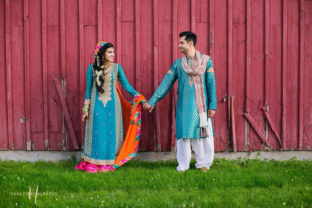 pakistani bride and groom in bleu lehenga and shirwani holding hands and standing in front of red barn in industrial farm in ottawa