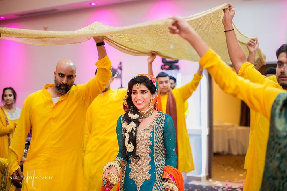 bride enteres mehendi reception under yellow dupatta in ottawa