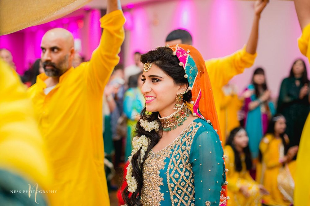 bride smiling as she entered the mehendi under yellow dupatta