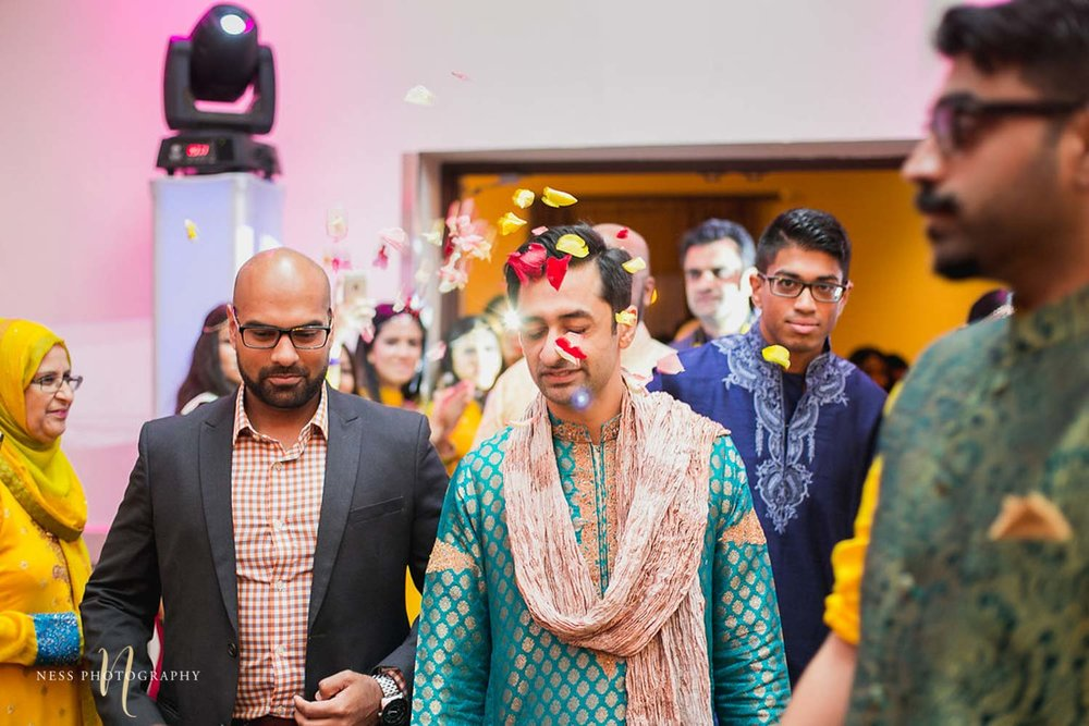 guests throw flower petals as the pakistani groom enteres the mehendi reception in baraat