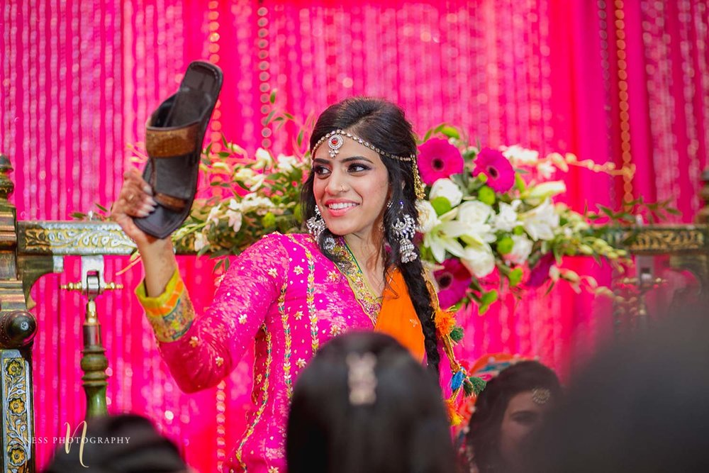 sister of the bride steals pakistani groom's shoe swhile playing joota chupai at mehendi