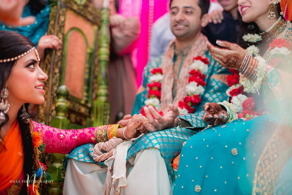 sister of the bride holding grooms hand playing joota chupai at mehendi