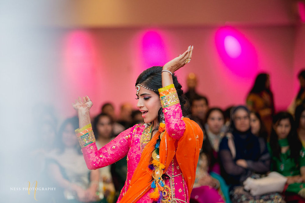 sister of the bride in pink shalwar kameez dancing at mehendi