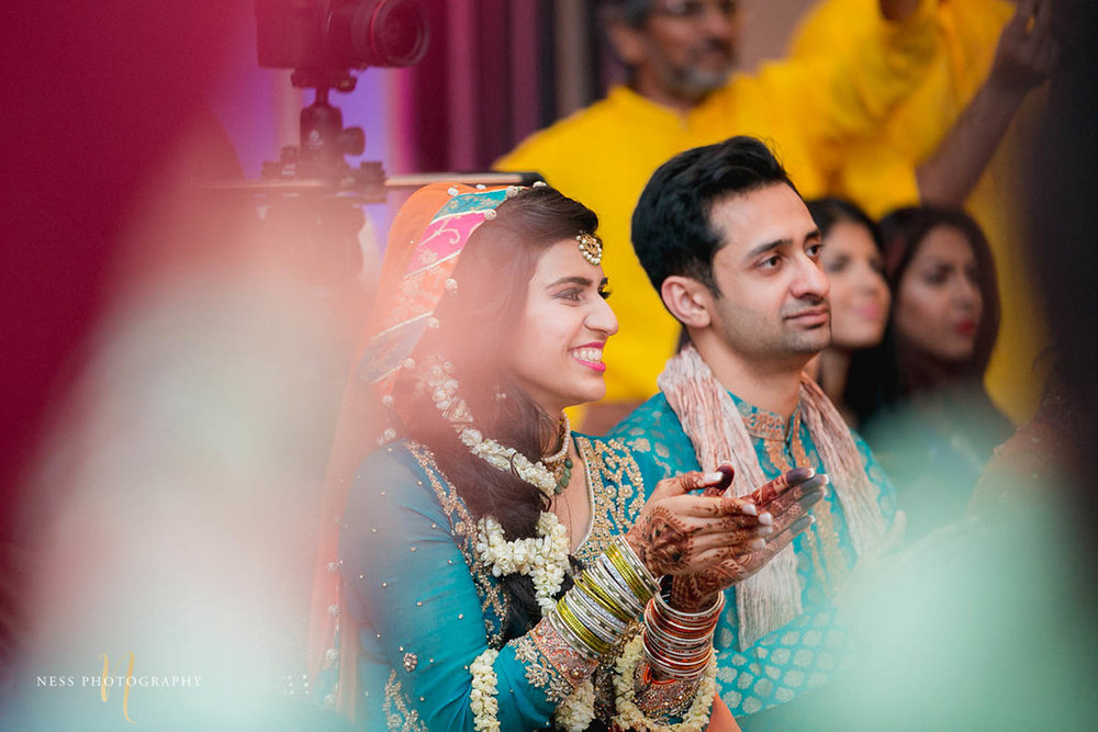 bride applauding as she watches bollywood performance at mehendi