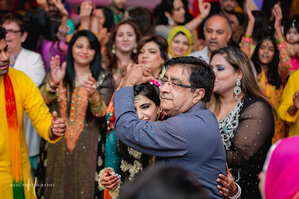 pakistani father dancing with his daughter and holding her at the mehendi in ottawa