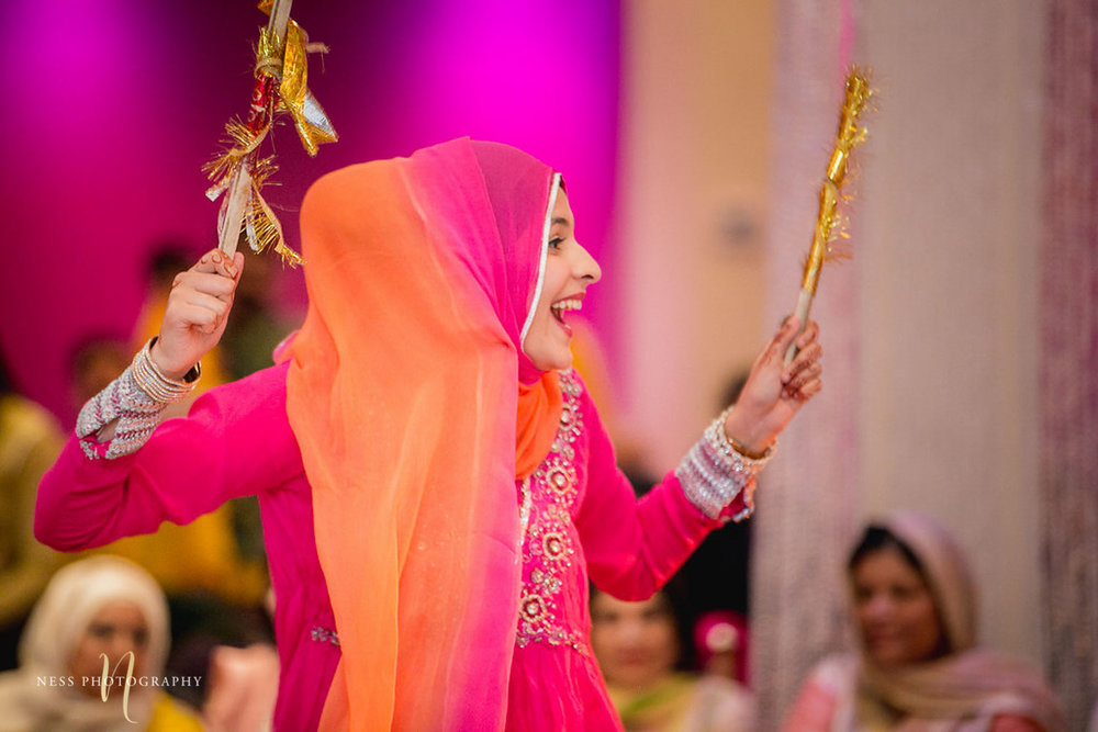 sister of the groom dancing dholki at the mehdni holding sticks