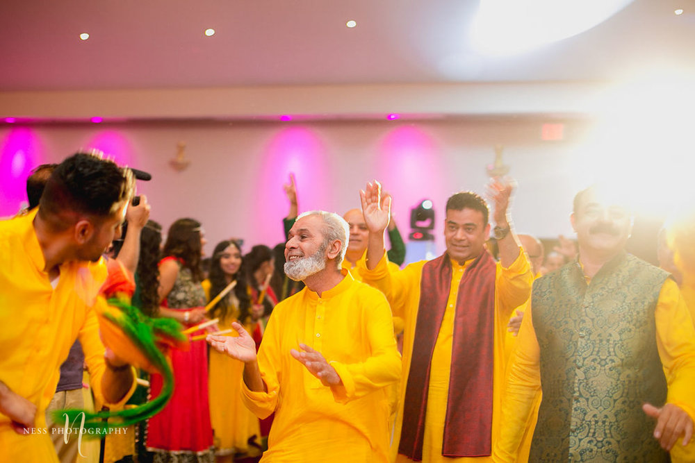 old guest dancing at pakistani mehendi in ottawa with light flare in the back