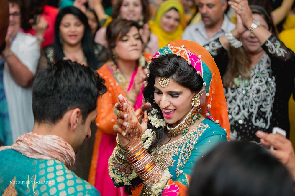 bride and groom dancing at their mehendi and the bride applauding
