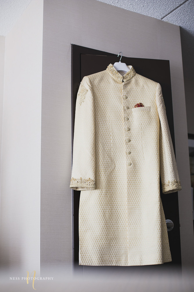 white sherwani hanging from the door for pakistani groom getting ready in ottawa