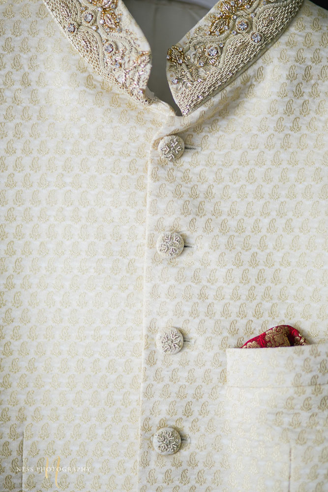closeup of sherwani handing with embroidered buttons and red pocket square
