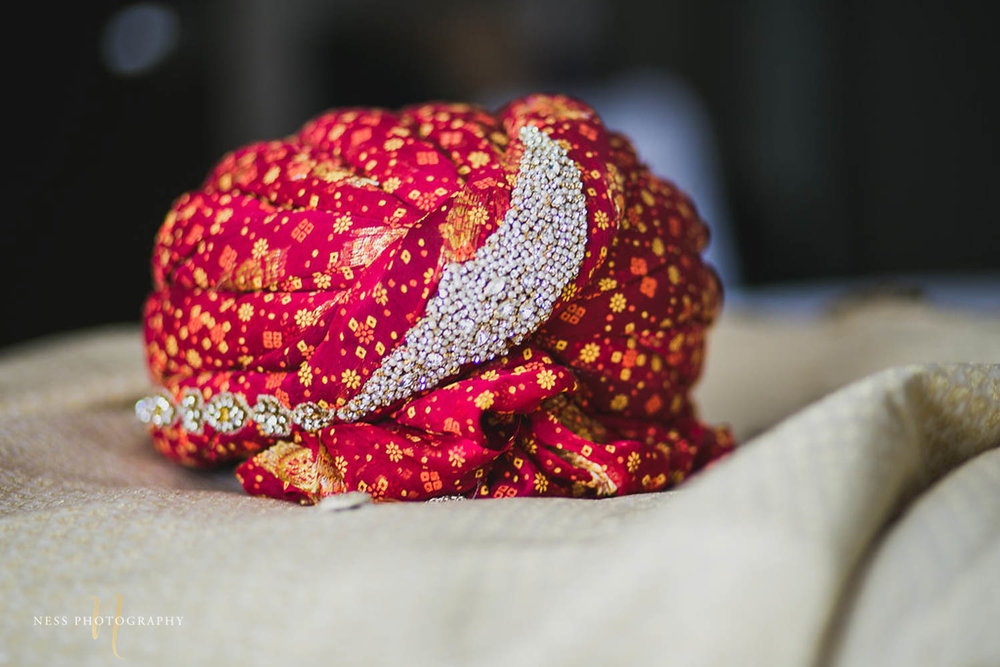 red turban on the bed for the groom to put on during pakistani wedding nikkah