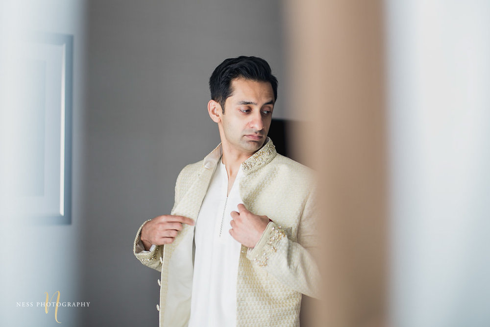 groom facing the window and putting on his sherwani while looking to the side getting ready for pkistani nikkah reception in ottawa