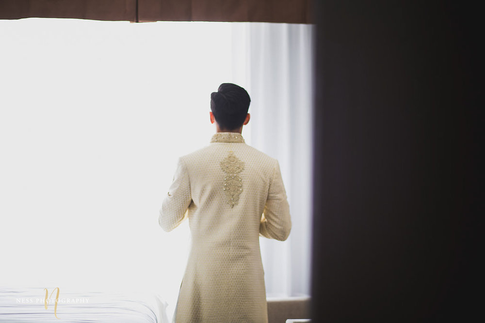 image from the back of the groom facing the window dressing up for pakistani nikkah in ottawa