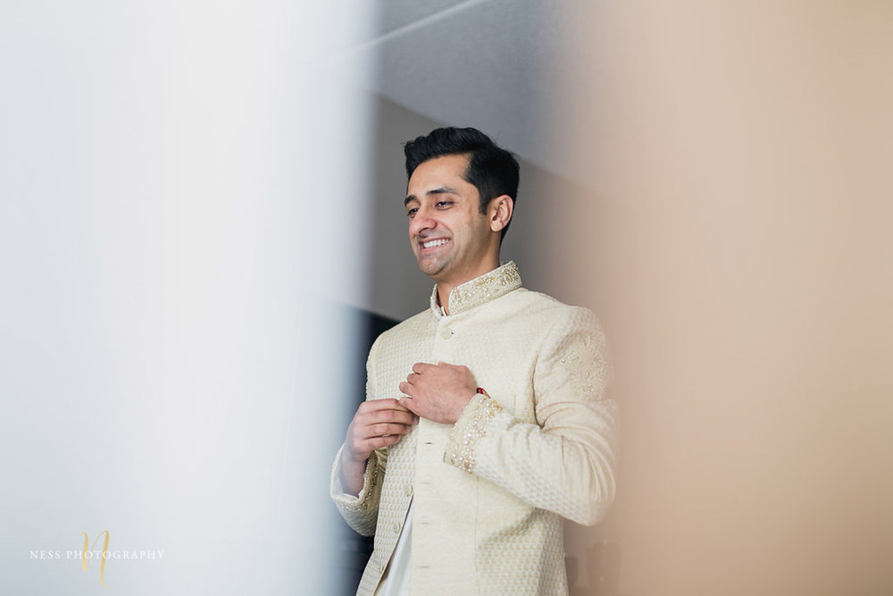 groom buttoning his sherwani and smiling