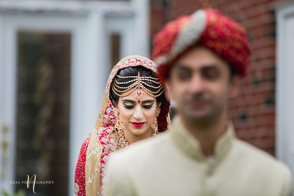 groom blurry in the fron abd pakistani bride in red lehenga in the background walking towards him for first look