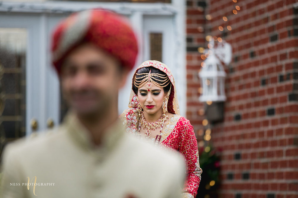 pakistani bride in red lehenga walking towards the groom for first look