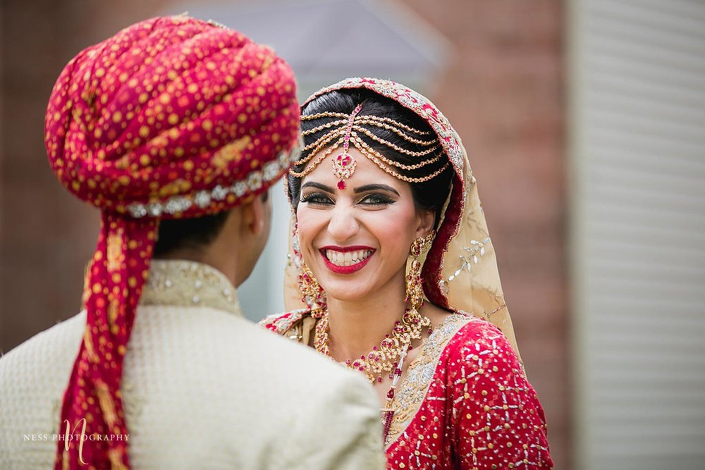 bride in red lehenga looking at the camera and smiling after pakistani first look