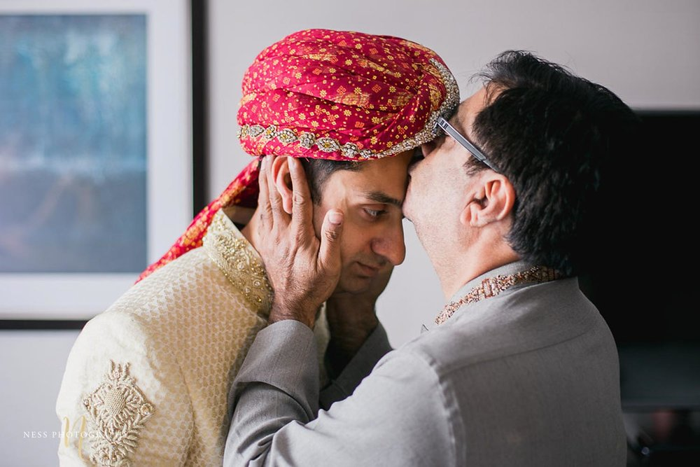 father of the groom kissing the forehead of the son while he is getting ready for nikkah in ottawa