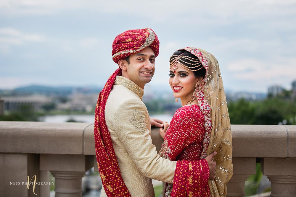 bride in red lehenga and groom in pale white sherwani looking back at the camera with ottawa city in the background