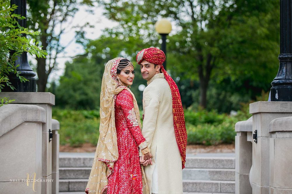 bride and groom holding hands and looking back at the camera at major's hill park in ottawa on nikkah day