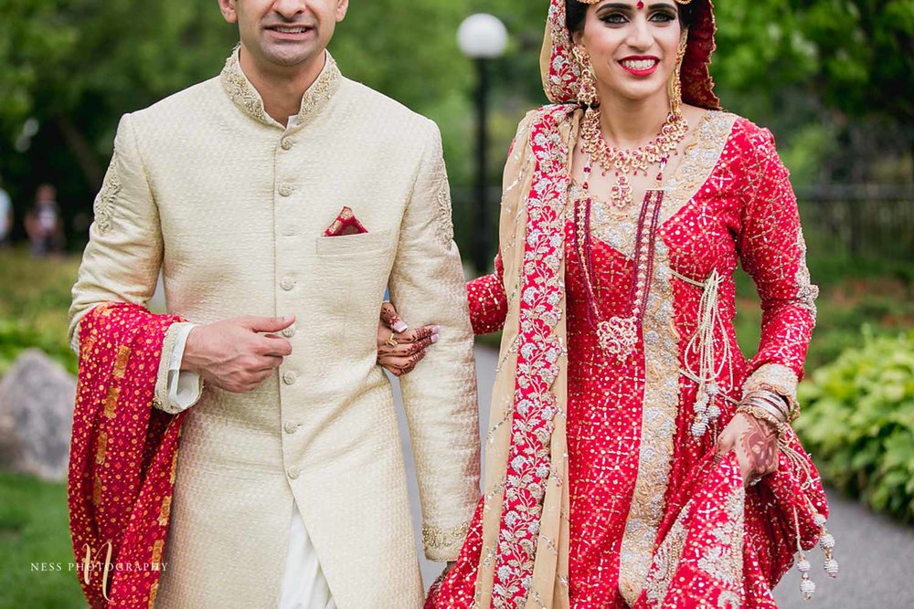 bride in red lehenga holding groom's hand walking towards major's hill park for pakistani bridal photos