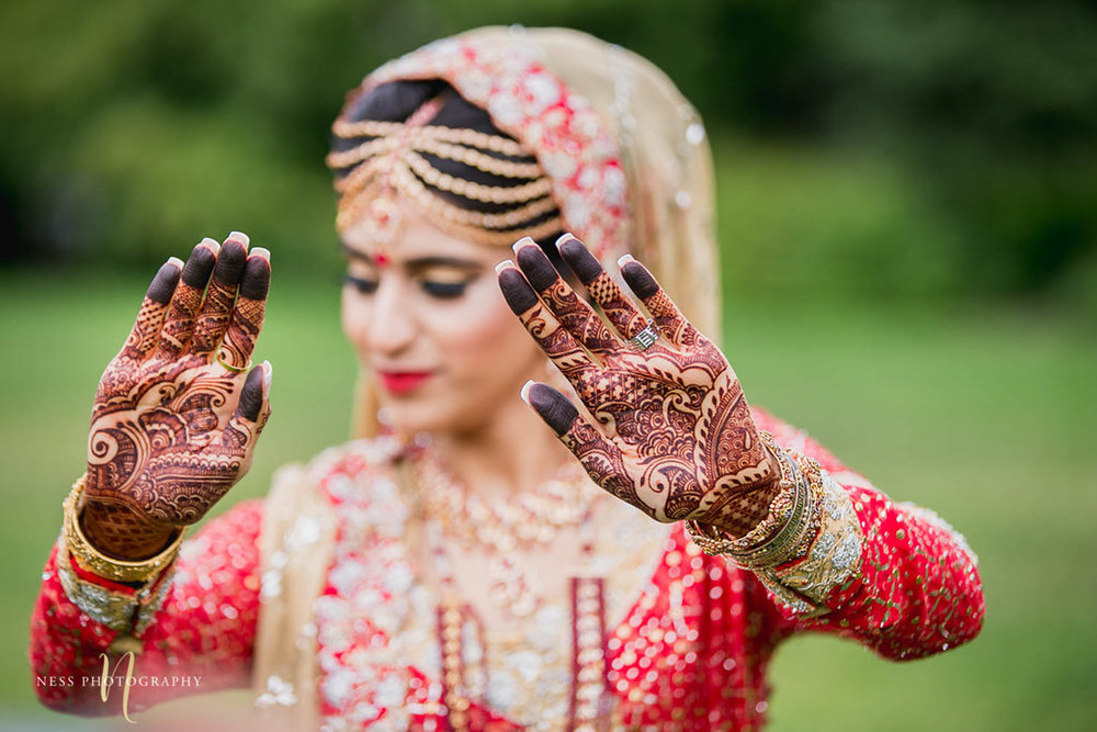 pakistani bride in red lehenga holding her hands up and showing her mehendi during bridal photoshoot in ottawa