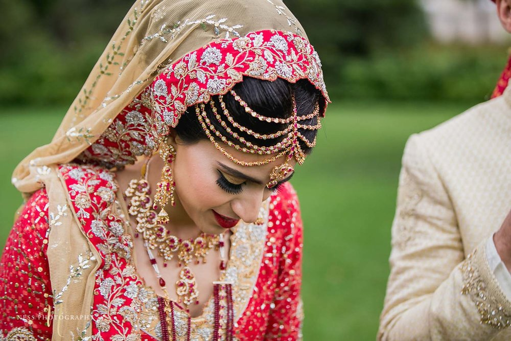 bride looking down showing her tikka and red dupatta during bridal photoshoot in major's hill park