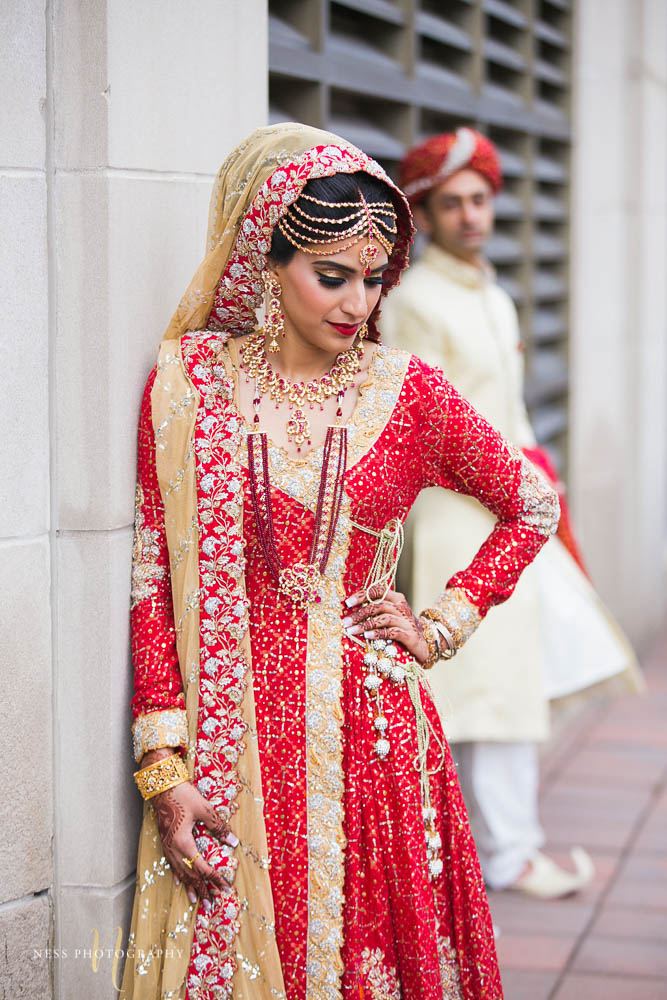 bride in red lehenga standing by the wall and looking down while groom in sherwani is blurry in the background