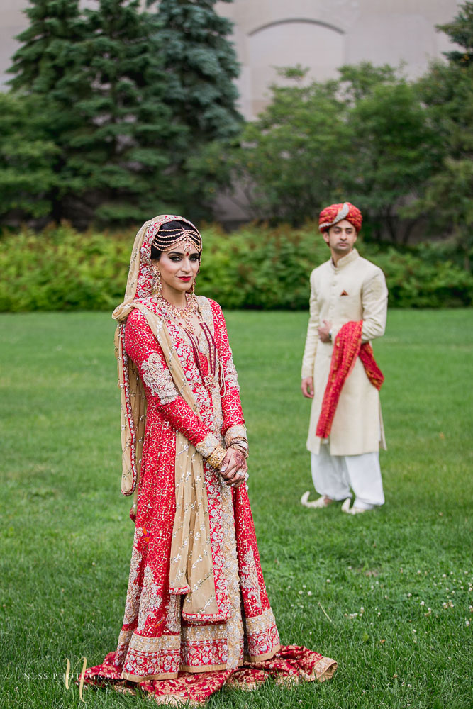 pakistani bride and groom striking a bollywood pose and standing in major's hill park in ottawa