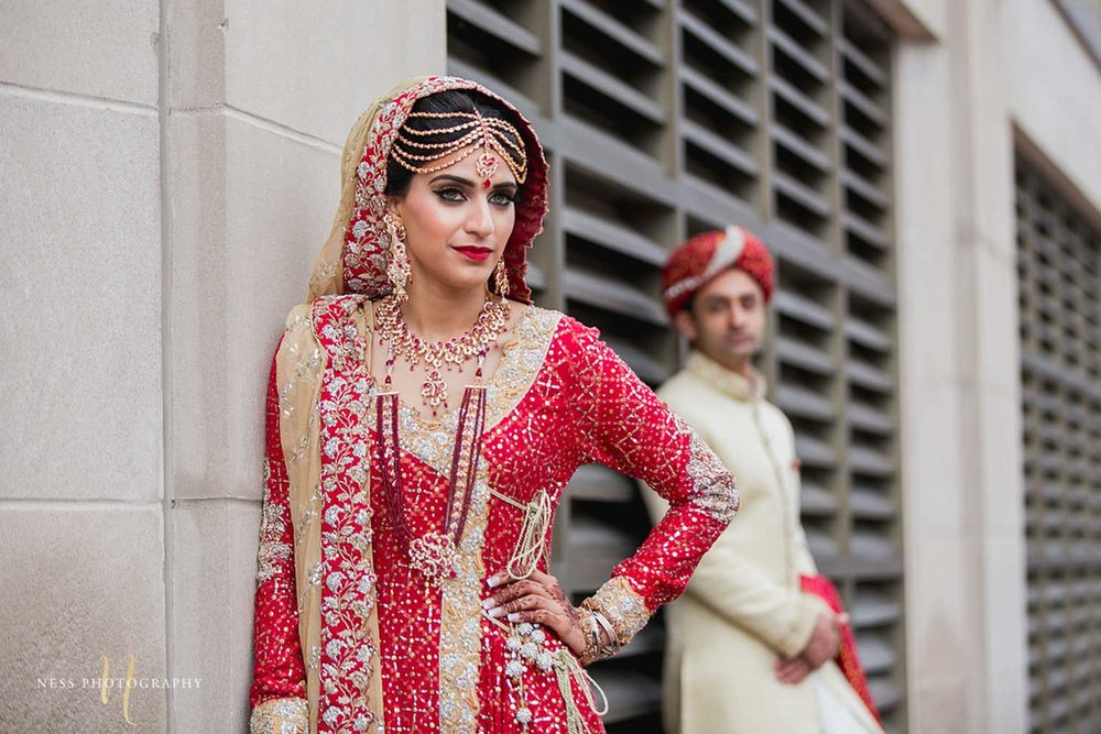pakistani bride in red lehenga in focus in the foreground and groom in the background during bridal photoshoot at chateau laurier